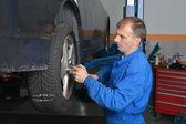 Mechanic changing car wheel — Stock Photo