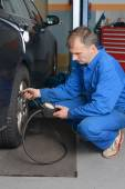 Tire pressure check. car mechanic inflating tyre — Stock Photo