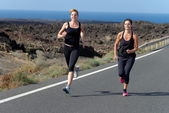 Two Runner women running on mountain road in beautiful nature — Stock Photo
