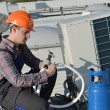 Young repairman fixing air conditioning system — Stock Photo #65706851