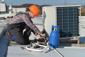 Young repairman fixing air conditioning system — Stock Photo