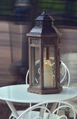 Lantern with a candle on a table at a cafe. — Foto de Stock