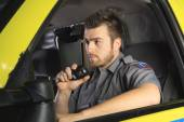 A paramedic at the wheel of his ambulance talking on microphone. — Stock Photo