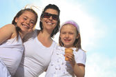 Family eating ici-cream in front of ocean — Stock Photo