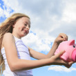A Piggy Bank and Coin holding by a little girl — Stock Photo #64946467