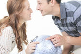 Excited young couple planning their holiday holding up a globe a — ストック写真