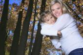 A Family enjoying golden leaves in autumn park — Stock Photo