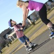 Active family - mother and kid having fun, rollerblading outdoor — Stock Photo #64986109