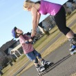 Active family - mother and kid having fun, rollerblading outdoor — Stock Photo #64986153