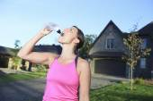 A woman jogging in a urban place with house in the background — Stock Photo