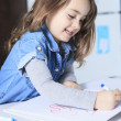 Cheerful little girl colouring at the table at home in kitchen — Stock Photo #65011009