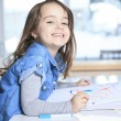 Cheerful little girl colouring at the table at home in kitchen — Stock Photo #65011031