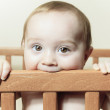 Funny little baby with beautiful standing in a round white crib — Stock Photo #65011593
