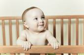 Funny little baby with beautiful standing in a round white crib — Stock Photo
