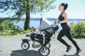 A Young mother jogging with a baby buggy — Stock Photo