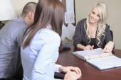 Jong paar in een vergadering - verzekering of bank voor investeringen — Stockfoto