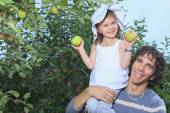 A girl and her daddy with apple background — Stock Photo