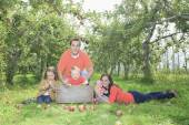 A happy family of four attractive caucasian catch apple on a fie — Stock Photo