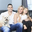 A Family with pets sit on sofa at home — Stock Photo #65224613