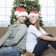A Christmas Couple wearing Santas Hats. Smiling Family Celebrat — Stock Photo #65225989