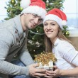 A Christmas Couple wearing Santas Hats. Smiling Family Celebrat — Stock Photo #65225995