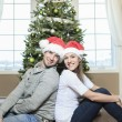A Christmas Couple wearing Santas Hats. Smiling Family Celebrat — Stock Photo #65225999