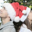 A Christmas Couple wearing Santas Hats. Smiling Family Celebrat — Stock Photo #65226015