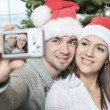 A Christmas Couple wearing Santas Hats. Smiling Family Celebrat — Stock Photo #65226037
