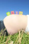 Alphabet blocks spelling BABY on a pregnant belly — Foto Stock