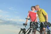 A senior man and a woman on bike at the sunset. — Stock Photo