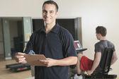 Homem de treinador pessoal de mulher de ginásio com equipamento de treinamento de peso — Fotografia Stock