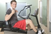 A man cycling on exercise bike in gym — ストック写真