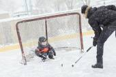 A family playing at the skating rink in winter. — Stock Photo