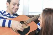 A Handsome man serenading his girlfriend with guitar at home in — Stock Photo