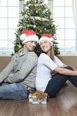 A Christmas Couple wearing Santas Hats. Smiling Family Celebrat — Stock Photo