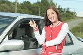 Car driver woman happy showing car keys out window — Zdjęcie stockowe
