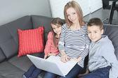 Afbeelding van vriendelijke familie zittend op de Bank en kijken naar lapt — Stockfoto