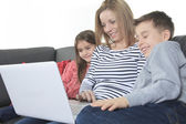Image of friendly family sitting on the sofa and looking at lapt — Stock Photo