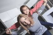 A Mother with daughter standing in kitchen. Interior portrait. — Stockfoto