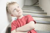 Neglected lonely child leaning at the wall — Stock Photo
