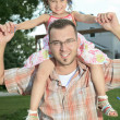 Father and daughter.Young man holding a little girl on shoulders — Stock Photo #65377263