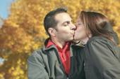 A loving couple sitting on bench in autumn background — Stock Photo