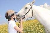A white horse on yellow flower field with a rider. — Stock Photo