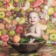 Happy little baby girl with fruits on the basket — Stock Photo #65384801
