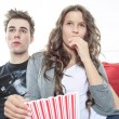 Close up portrait of young couple sitting together on a sofa at home watching television, joyfully smiling eating pop corn enjoying a night in together. Home lifestyle and entertainment technology. — Stock Photo #65388427