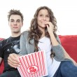 Close up portrait of young couple sitting together on a sofa at home watching television, joyfully smiling eating pop corn enjoying a night in together. Home lifestyle and entertainment technology. — Stock Photo #65388449