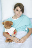 Little girl in hospital bed with teddy bear — Stock Photo