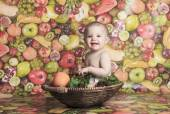 Happy little baby girl with fruits on the basket — Stock Photo