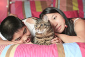 Asian kid lay on his bedroom with cat — Stock Photo