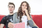 Close up portrait of young couple sitting together on a sofa at home watching television, joyfully smiling eating pop corn enjoying a night in together. Home lifestyle and entertainment technology. — Stock Photo